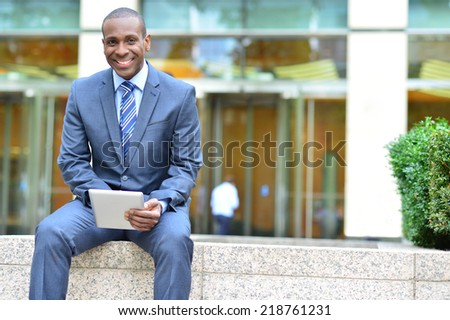 Businessman using his digital tablet at outdoors - stock photo