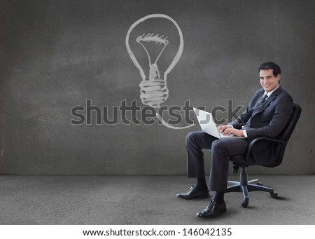 Businessman using his laptop with arrow graphic coming from it in empty grey room - stock photo