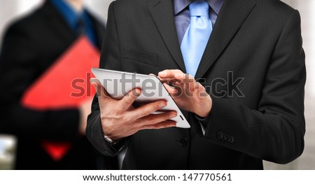 Businessman using his tablet - stock photo