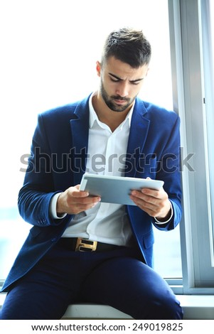 Businessman using his tablet in the office - stock photo