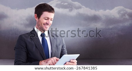 Businessman using his tablet pc against clouds in a room - stock photo