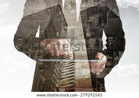 Businessman using his tablet pc against low angle view of skyscrapers - stock photo