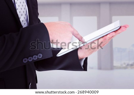 Businessman using his tablet pc against room overlooking ocean - stock photo