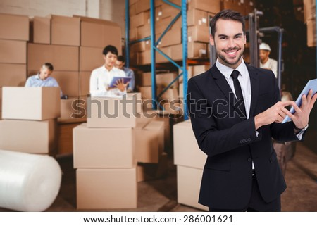 Businessman using his tablet while looking at the camera against people at work in warehouse - stock photo