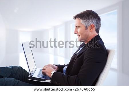 Businessman using laptop against bright white corridor with windows - stock photo