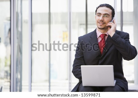 Businessman using laptop and mobile phone outside - stock photo