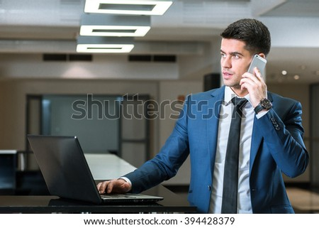Businessman using laptop and talking on cellphone, standing in modern office