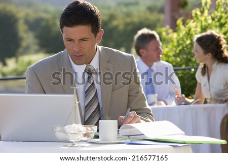 Businessman using laptop at caf�½ - stock photo