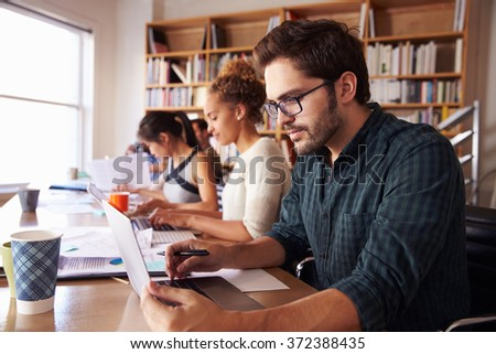 Businessman Using Laptop At Desk In Busy Office - stock photo