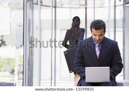 Businessman using laptop computer outside office - stock photo
