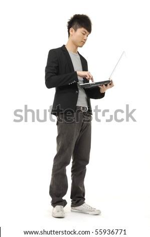 Businessman using laptop computer, standing - stock photo