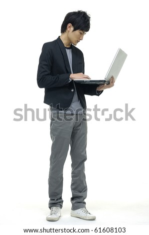 Businessman using laptop computer, standing,