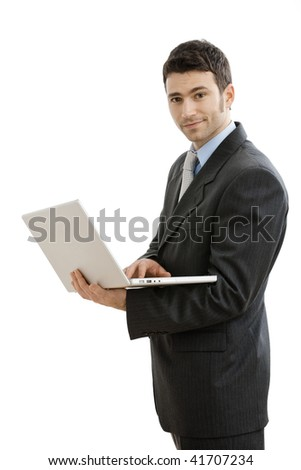 Businessman using laptop computer, standing, smiling. Isolated on white background. - stock photo