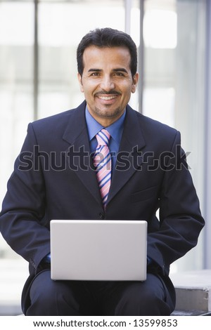 Businessman using laptop coomputer outside office - stock photo