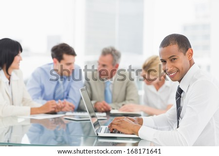 Businessman using laptop during a meeting smiling at camera in the office