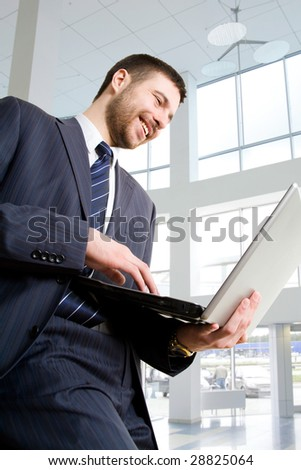 Businessman using laptop in business building - stock photo