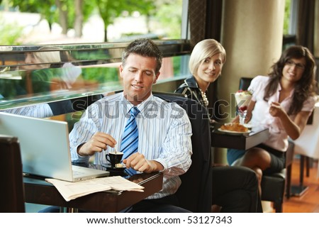 Businessman using laptop in cafe, young women in the background recognized him. Selective focus on businessman. - stock photo