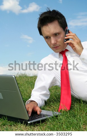 Businessman using laptop outdoors - stock photo