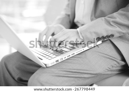 Businessman using laptop pc. He is sitting on a stairs. - stock photo