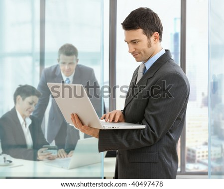 Businessman using laptop standing in office, businesspeople working at desk in the background. - stock photo