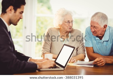 Businessman using laptop while senior couple is reading documents at home - stock photo