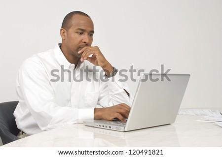 Businessman using laptop while sitting at desk - stock photo
