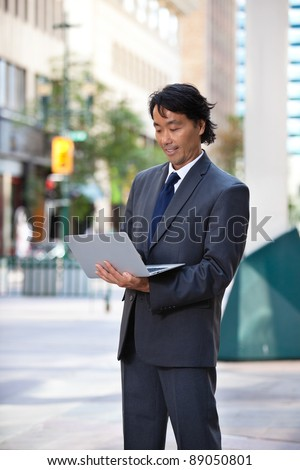 Businessman using laptop while standing on street - stock photo
