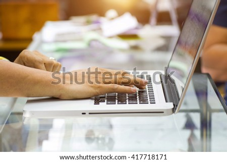 Businessman using laptop with tablet and pen on wooden table in coffee shop with a cup of coffee - stock photo