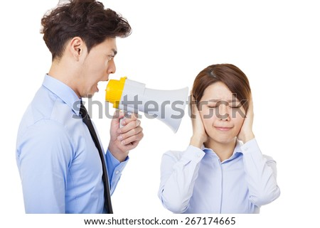 Businessman using megaphone to scream at businesswoman - stock photo
