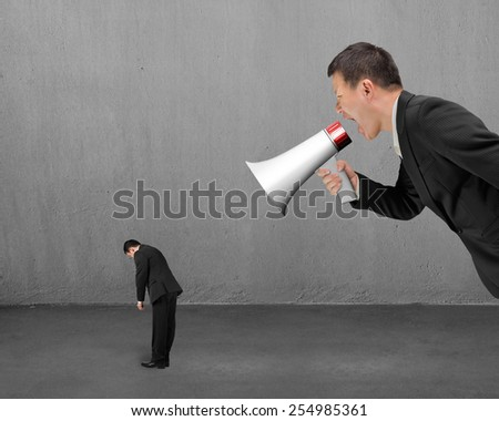 Businessman using megaphone yelling at his employee with concrete room background - stock photo