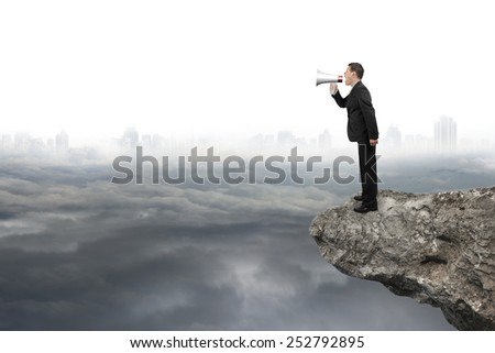 Businessman using megaphone yelling on cliff with gray cloudy cityscape background - stock photo