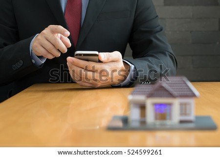 Businessman using mobile application for house property rental