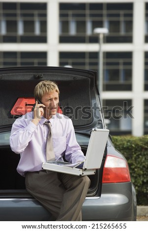 Businessman using mobile phone and laptop, sitting on open boot of stationary car - stock photo