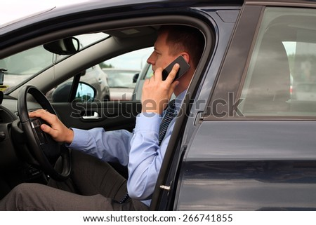 businessman using mobile smart phone while driving the car