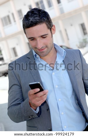 Businessman using mobilephone out in town - stock photo