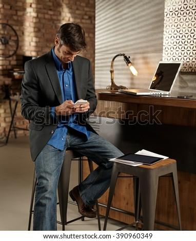 Businessman using mobilephone, sitting on barstool. - stock photo