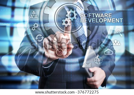 businessman using modern computer and select software development icon on virtual screen. business, technology and internet concept. - stock photo