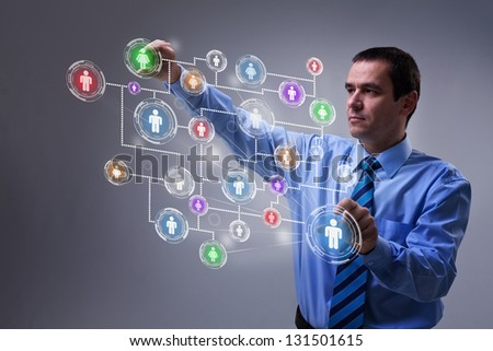 Businessman using modern social networking interface on virtual screen - stock photo