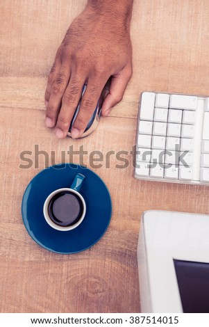 Businessman using mouse by coffee cup while working at table in office - stock photo