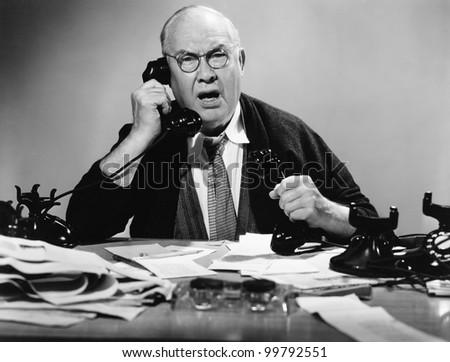 Businessman using multiple phones - stock photo