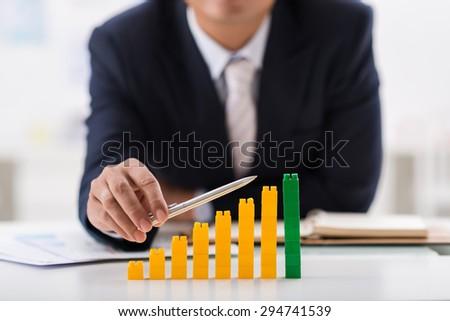 Businessman using pen to indicate ascending bar graph - stock photo