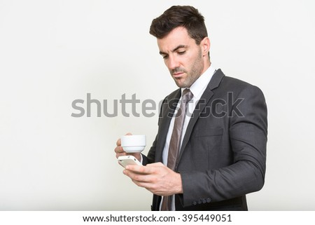 Businessman using phone and holding coffee cup