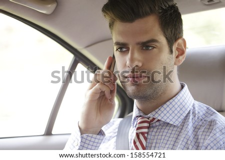 Businessman using phone in his car  - stock photo
