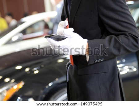 Businessman using phone outside the car. - stock photo
