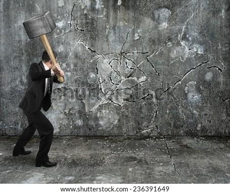 businessman using sledgehammer cracking wall broken on concrete floor background - stock photo