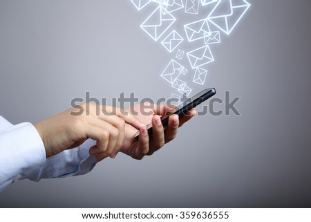 Businessman using smart phone with Email icons against gradually varied background. - stock photo