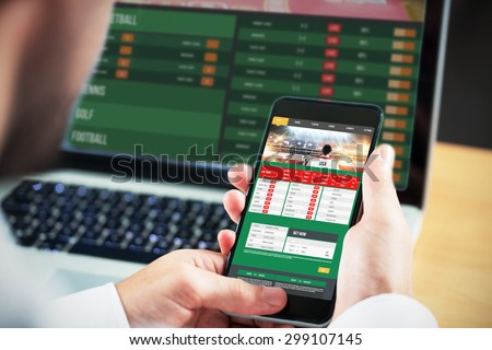Businessman using smartphone against gambling app screen - stock photo
