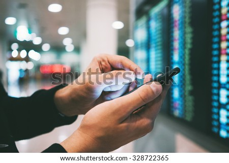 Businessman using smartphone and checking flight information at airport - stock photo