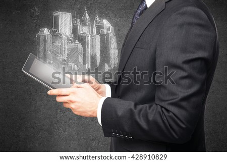 businessman using tablet and drawing highrise on wall - stock photo