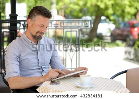 Businessman using tablet in cafe - stock photo